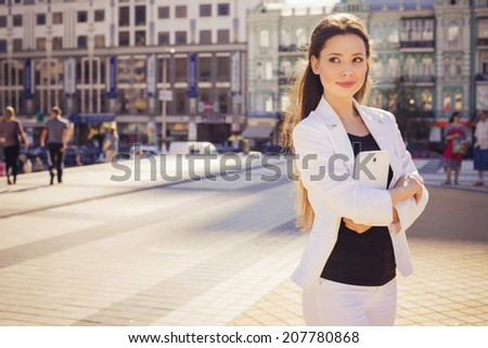 Beautiful brunette business woman in white suit working on a tablet in her hands outdoors. copy space - stock photo