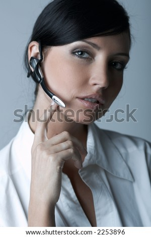 Beautiful brunette business woman with wireless headset isolated on clear background