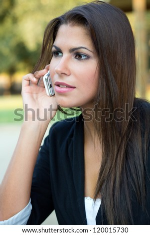 Beautiful brunette businesswoman talking by cellphone in the park - stock photo