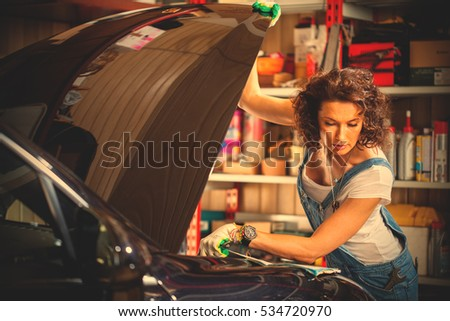 beautiful brunette car mechanic in blue overalls reading instruction engine adjustment near a car with an open hood. Preparing for autotravel. instagram image filter retro style