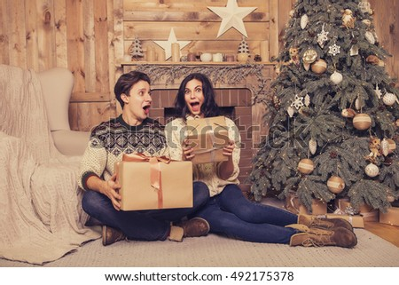 Beautiful brunette caucasian romantic loving couple in cozy warm sweaters in the cabin on a christmas new year eve, smiling, kissing, having fun with each other. Dim dark night light, toned image