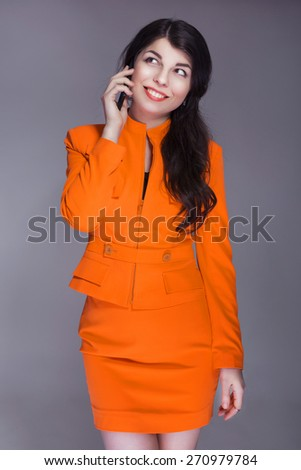 Beautiful brunette caucasian woman in orange stylish business suit talking on the phone. grey neutral background - stock photo