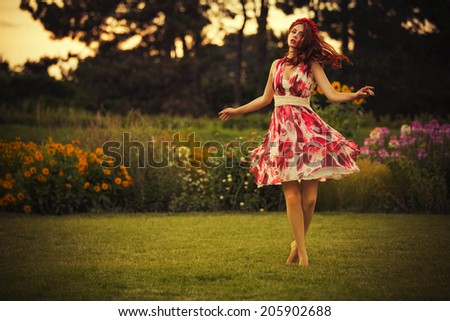 Beautiful brunette caucasian woman in white and red dress at the park in red and yellow flowers on a summer sunset dancing in the meadow. Copy Space - stock photo