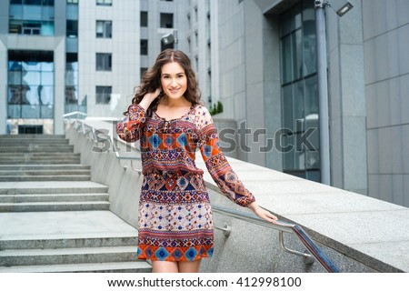 Beautiful brunette caucasian young woman wearing dress with ethnic print and walking on the street. Girl in boho style. Fashionable stylish girl on the background of the business center. Smiling girl. - stock photo