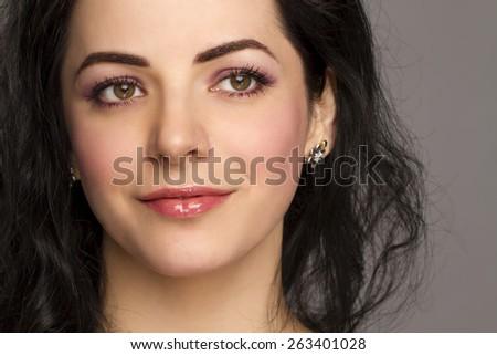 beautiful brunette close-up on gray background - stock photo