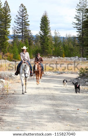 Beautiful brunette cowboy and cowgirl on a mountain trail ride - stock photo