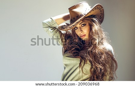 Beautiful brunette cowgirl posing in studio, wearing big hat, looking at camera - stock photo