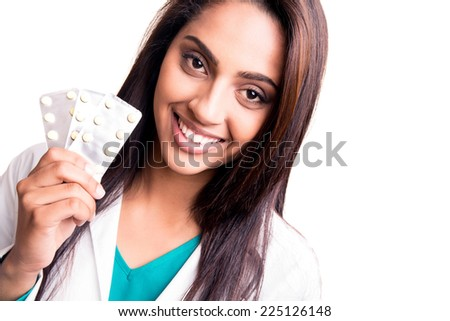 Beautiful brunette doctor showing sealed blisters over white - stock photo