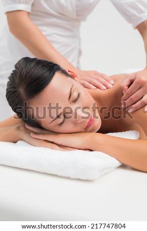 Beautiful brunette enjoying a back massage in the health spa - stock photo