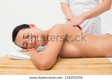 Beautiful brunette enjoying a back massage in the health spa