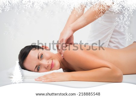 Beautiful brunette enjoying a back massage smiling at camera against fir tree forest and snowflakes - stock photo