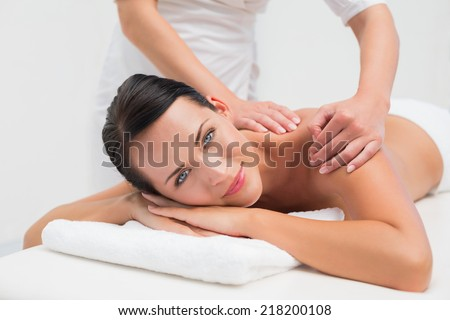 Beautiful brunette enjoying a back massage smiling at camera in the health spa - stock photo