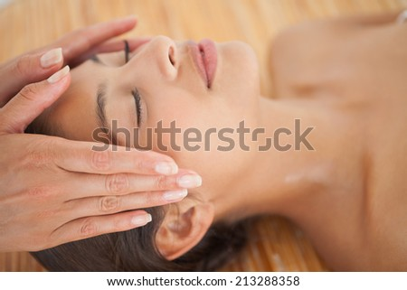 Beautiful brunette enjoying a head massage at the health spa - stock photo