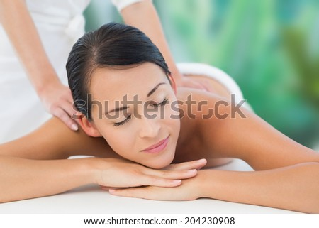 Beautiful brunette enjoying a shoulder massage at a luxury spa - stock photo