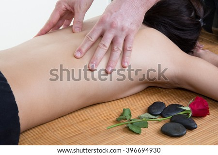 Beautiful brunette enjoying a shoulder massage in the health spa