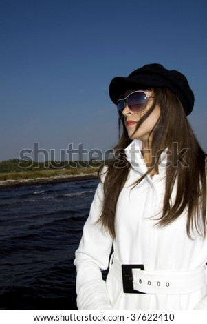 Beautiful brunette fashion model with a white coat, black beret and sunglasses standing by the sea