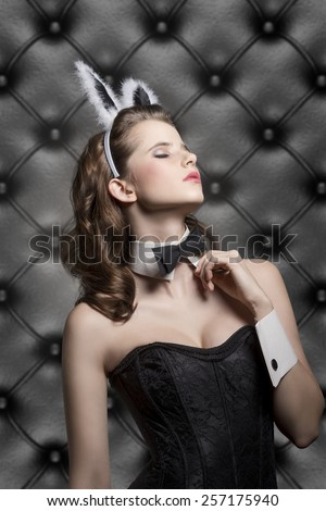 beautiful brunette female in sensual pose in glamour ester shoot with bunny ears, corset and black papillon, wearing like sexy playgirl  - stock photo