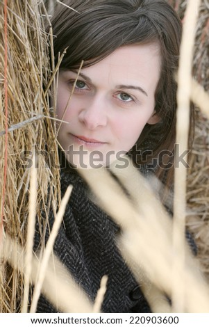Beautiful brunette female sitting against a hay bale  - stock photo