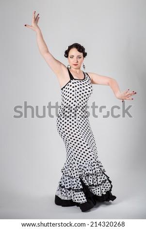 beautiful brunette female spanish flamenco dancer in black and white flamenco dress dancing in studio on gray background - stock photo