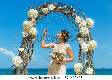Beautiful brunette fiancee in white wedding dress with big long white train and with wedding bouquet stand on shore sea near the wedding arch of vines and flowers. Wedding and honeymoon concept. - stock photo