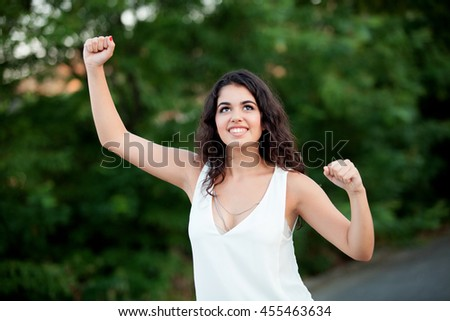 Beautiful brunette girl celebrating something in the park withmany plants of background - stock photo