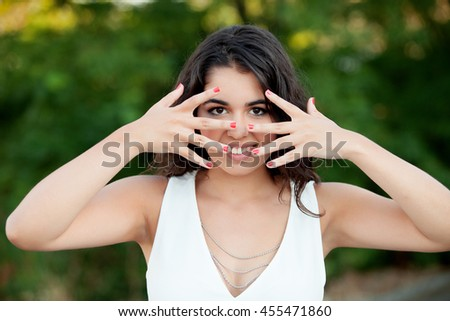Beautiful brunette girl covering her face in the park with many plants of background - stock photo