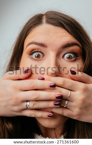 beautiful brunette girl covers her mouth with her hands - stock photo
