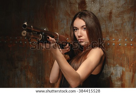 beautiful brunette girl dressed in black with a gun near the metal wall with rusty streaks shot from the distortion of proportions - stock photo