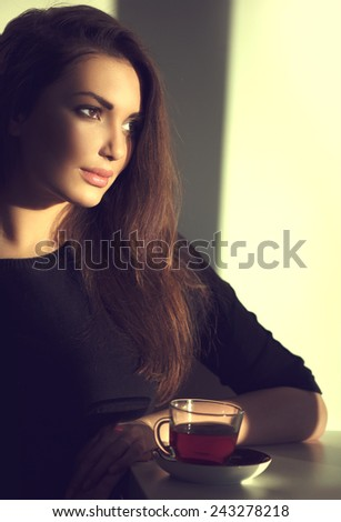 Beautiful Brunette Girl Drinking Tea or Coffee in Cafe. Beauty Model Woman with the Cup of Hot Beverage. Warm Colors Toned  - stock photo