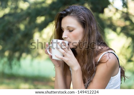 Beautiful Brunette Girl Drinking Tea or Coffee. Woman with a Cup. - stock photo