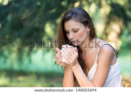 Beautiful Brunette Girl Drinking Tea or Coffee. Woman with Cup o - stock photo
