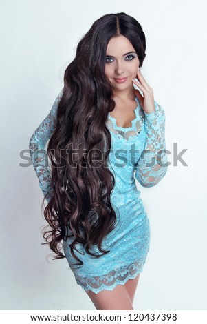 Beautiful Brunette Girl. Healthy Long Curly Hair. Lady in blue dress - stock photo