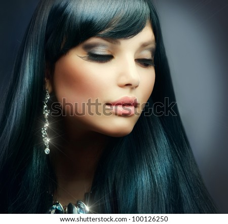 Beautiful Brunette Girl. Healthy Long Hair and Holiday Makeup. Jewelry - stock photo