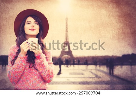 Beautiful brunette girl holding cup of coffee on Eiffel tower background - stock photo
