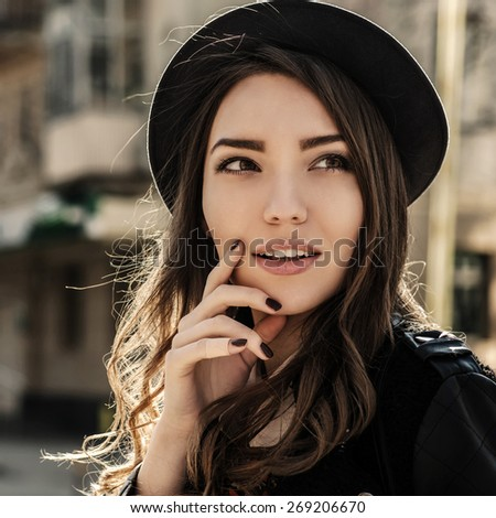 Beautiful brunette girl in casual clothes walking around the city. Fashion and city style. Facial expression.  - stock photo