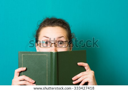 beautiful brunette girl in glasses with book - stock photo