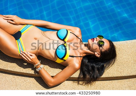 Beautiful brunette girl in good shape with long hair and tan perfect skin in white swimming suite with golden jewelry with lie near the pool with green water keeping open her eyes with soft smile - stock photo