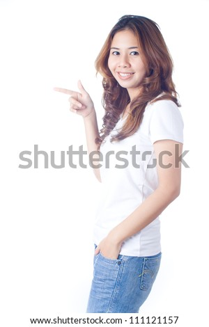 Beautiful brunette girl in jeans smiling and pointing to copy space on white background