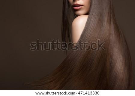 brunette cô gái xinh đẹp trong di chuyển với một mái tóc hoàn toàn trơn tru, make-up và cổ điển.  Vẻ đẹp khuôn mặt.  Ảnh chụp trong studio.