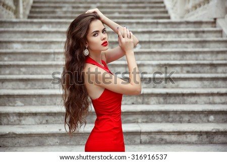 Beautiful brunette girl in red dress with long healthy hair posing on Staircase in Birth of our Lady Church, Montenegro
