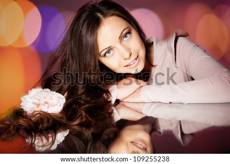 Beautiful brunette girl in studio with flower - stock photo