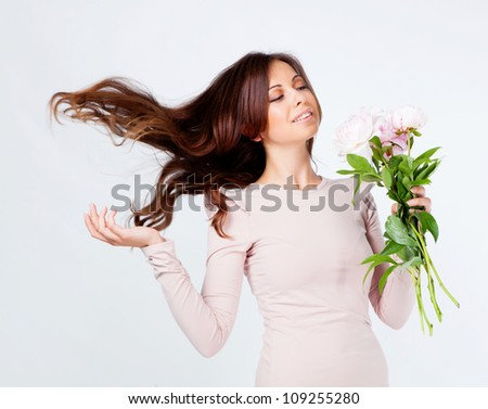 Beautiful brunette girl in studio with flower - stock photo