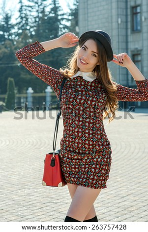Beautiful brunette girl in stylish dress jumps on the city square. Fashion and city style. Facial expression. - stock photo
