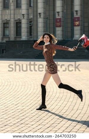 Beautiful brunette girl in stylish dress jumps on the city square. Fashion and city style. Facial expression. Various flags and the Orthodox Church on background. - stock photo