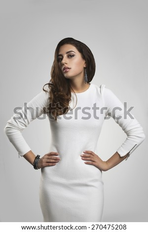 Beautiful brunette girl in white dress against gray background - stock photo