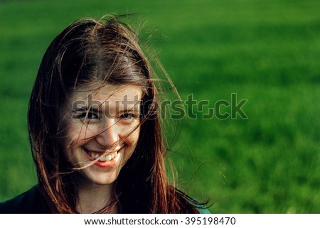 beautiful brunette girl in windy green field, sunny springtime, environment concept