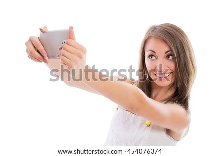 Beautiful brunette girl is photographed on a smartphone isolated on white background. Sexy young woman doing a selfie. - stock photo