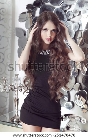 Beautiful brunette girl model with long hair in short black dress posing against mirrors wall at interior - stock photo