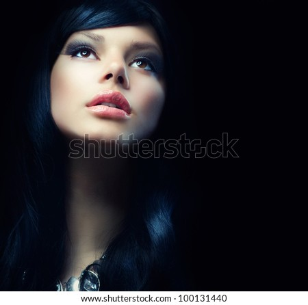 Beautiful  Brunette Girl over Black Background. Darkness - stock photo