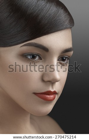 Beautiful brunette girl portrait with red lips against the dark background - stock photo
